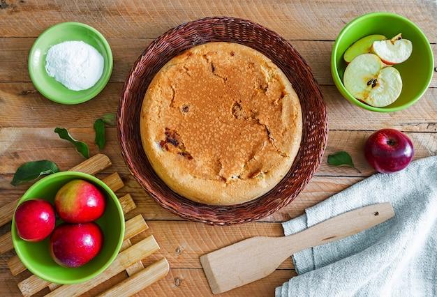 Hausgemachter apfelkuchen in einem korbteller auf einem holztisch mit kochzutaten herum