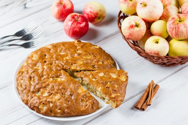 Hausgemachter apfelkuchen mit zimt und frischen reifen äpfeln im hintergrund