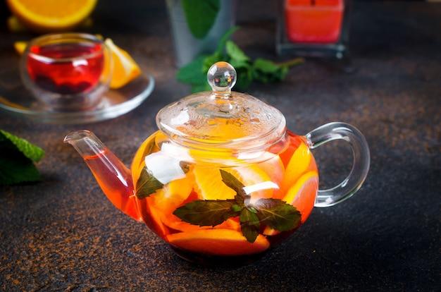 Hausgemachter aromatisierter früchtetee mit orangen- und zitronenscheibe, beeren, minze und honig in glasteekanne auf dunklem rustikalem hintergrund. heißes herbst- oder wintergetränk. tee aufbrühen,