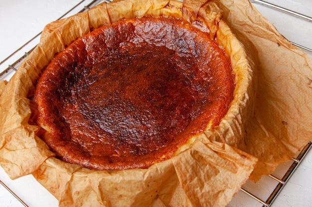 Hausgemachter baskischer gebrannter käsekuchen unmittelbar nach dem backen auf einem rost.