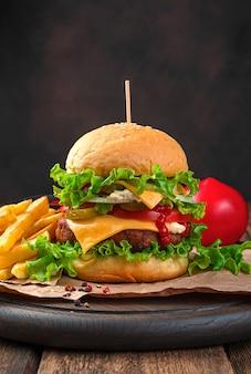 Hausgemachter burger mit rindfleisch-käse-tomaten und eingelegten gurken nahaufnahme auf einer braunen wand