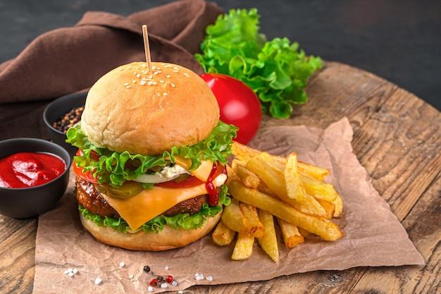 Hausgemachter burger mit rindfleisch, käse und gemüse an einer braunen wand. fastfood. horizontale ansicht, platz zum kopieren.