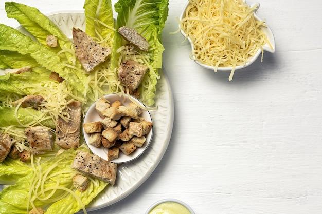 Hausgemachter caesar-salat mit romanine, käse, croutons, hühnchen, zitrone und sauce.