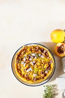 Hausgemachter chiffon-kuchen mit puddingcreme und nektarinen, dekoriert mit thymian und zuckerpulver.