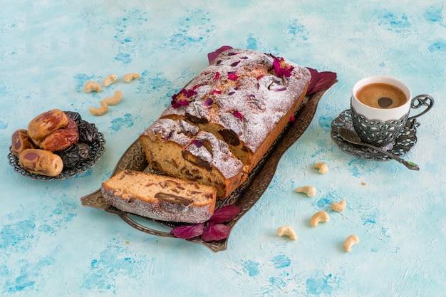 Hausgemachter dessertkuchen mit datteln und nüssen, serviert mit schwarzem kaffee