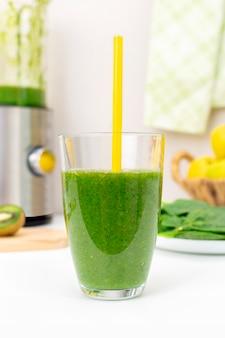 Hausgemachter detox grüner spinat-smoothie im glas mit trinkhalm. gesundes essen und abnehmen