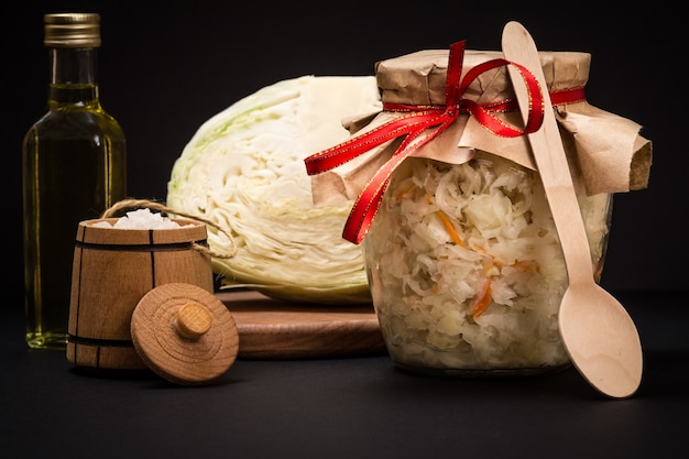 Hausgemachter fermentierter kohl im glasgefäß im schwarzen hintergrund. frischer kohlkopf, salz und eine flasche öl auf dem hintergrund. veganer salat. das gericht ist reich an vitamin u. nahrung für eine gute gesundheit.