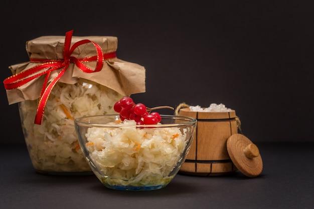 Hausgemachter fermentierter kohl in einer glasschüssel und einem glas, salz in einem kleinen holzfass auf schwarzem hintergrund. veganer salat. das gericht ist reich an vitamin u. nahrung für eine gute gesundheit.