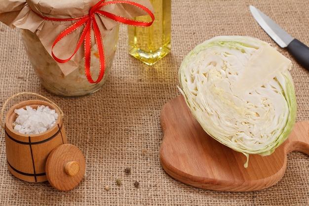 Hausgemachter fermentierter kohl mit karotte im glas, frischer kohlkopf, salz und eine flasche öl auf dem sacktuch. veganer salat. das gericht ist reich an vitamin u. nahrung für eine gute gesundheit.