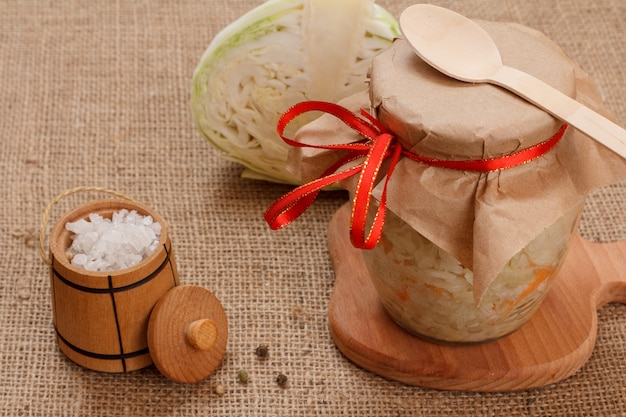 Hausgemachter fermentierter kohl mit karotte im glas, salz in einem kleinen holzfass und frischem kohlkopf auf dem sack. veganer salat. das gericht ist reich an vitamin u. nahrung für eine gute gesundheit.