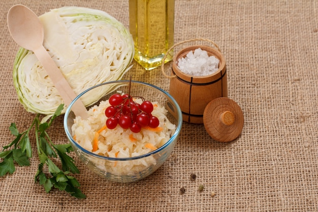 Hausgemachter fermentierter kohl mit karotte in glasschüssel, frischer kohlkopf, salz und eine flasche öl auf dem sacktuch. veganer salat. das gericht ist reich an vitamin u. nahrung für eine gute gesundheit.
