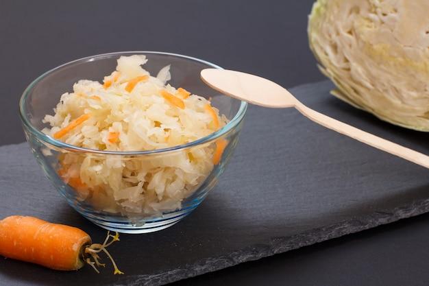 Hausgemachter fermentierter kohl mit karotte in glasschüssel mit frischem kohlkopf auf schwarzem hintergrund. veganer salat. das gericht ist reich an vitamin u. nahrung für eine gute gesundheit.