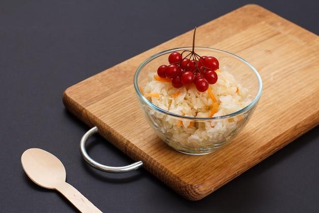 Hausgemachter fermentierter kohl mit karotte in glasschüssel mit viburnum-cluster auf schwarzem hintergrund. veganer salat. das gericht ist reich an vitamin u. nahrung für eine gute gesundheit.