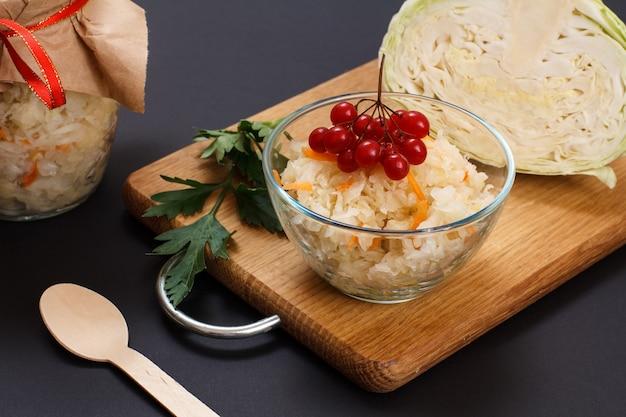 Hausgemachter fermentierter kohl mit karotte und viburnum-cluster in glasschüssel. frischer kohlkopf und glas im hintergrund. veganer salat. das gericht ist reich an vitamin u. nahrung für eine gute gesundheit.