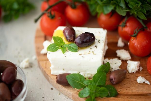 Hausgemachter feta-käse mit olivenöl, tomaten und basilikum auf einem holzbrett