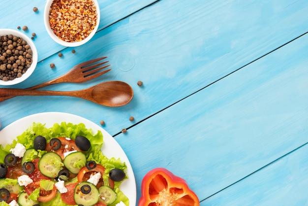 Hausgemachter frisch zubereiteter griechischer salat auf einer blauen fläche mit verschiedenen gewürzen.