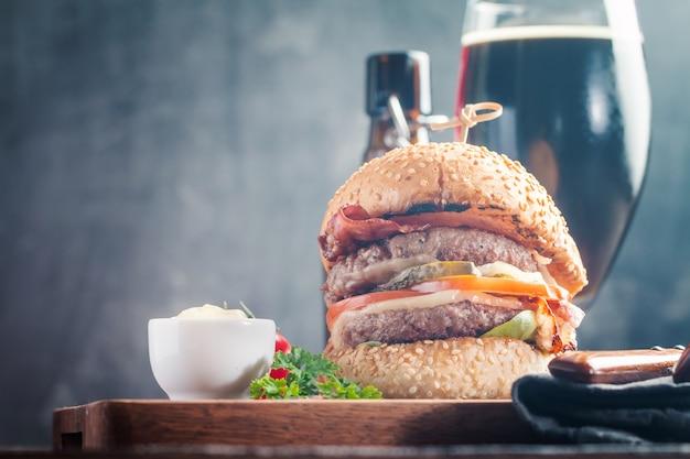 Hausgemachter frischer hamburger und dunkles bier auf holz