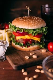 Hausgemachter frischer leckerer burger mit salat und käse auf rustikalem holztisch. pommes frites, tomaten und sauce. dunkler nahrungsmittelhintergrund.