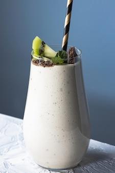 Hausgemachter fruchtjoghurt in glasschale mit tubulus im inneren, milchiges dessertgetränk mit kiwi, banane und schokolade