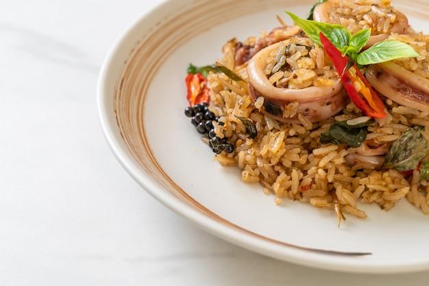 Hausgemachter gebratener basilikum- und würziger kräuterreis mit tintenfisch oder oktopus - asiatische küche