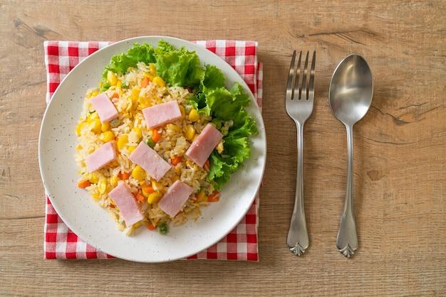 Hausgemachter gebratener reis mit schinken und gemischtem gemüse (karotte, grüne bohnen, karotte)