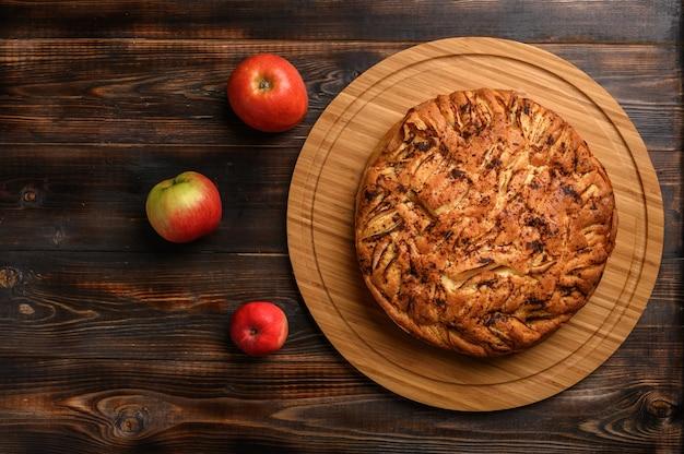 Hausgemachter gesunder traditioneller kornischer apfelkuchen auf braunem hintergrund