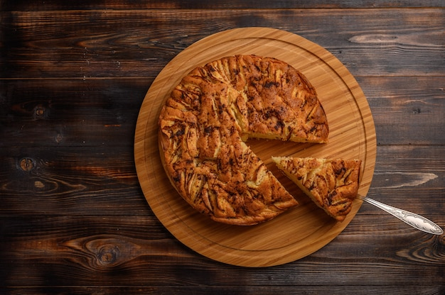 Hausgemachter gesunder traditioneller kornischer apfelkuchen mit einem abgeschnittenen stück auf dem schulterblatt