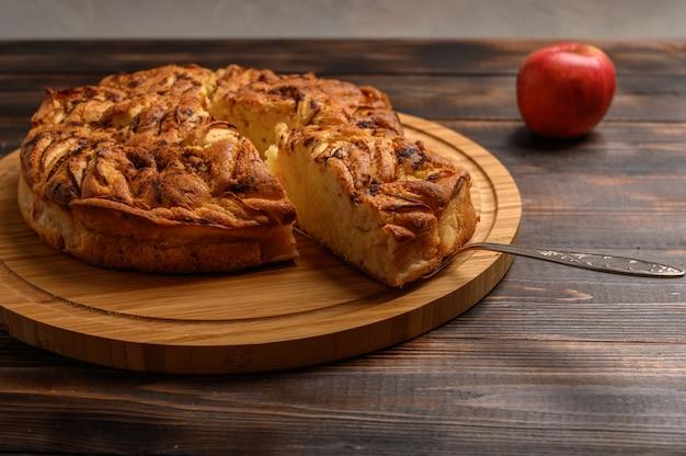 Hausgemachter gesunder traditioneller kornischer apfelkuchen mit einem geschnittenen stück auf dem schulterblatt auf braunem hintergrund