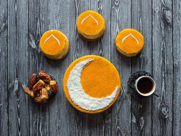 Hausgemachter goldener kuchen mit halbmond, serviert mit schwarzem kaffee und datteln. ramadan tisch