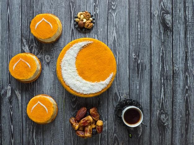 Hausgemachter goldener kuchen mit halbmond, serviert mit schwarzem kaffee und datteln. ramadanwand