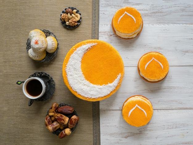 Hausgemachter goldener kuchen mit halbmond, serviert mit schwarzem kaffee und datteln