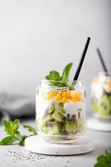 Hausgemachter griechischer joghurt mit kiwi- und mangoscheiben in einem glas, nahaufnahme