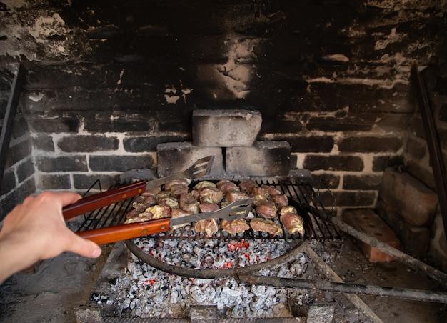 Hausgemachter grill im kamin. braten von fleisch auf einem gitter. gemütliche atmosphäre und hausmannskost.