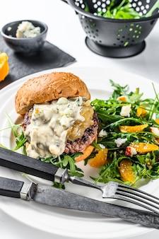 Hausgemachter hamburger mit blauschimmelkäse, marmorade und marmelade aus zwiebeln, eine beilage aus salat mit rucola und orangen. weißer hintergrund. draufsicht