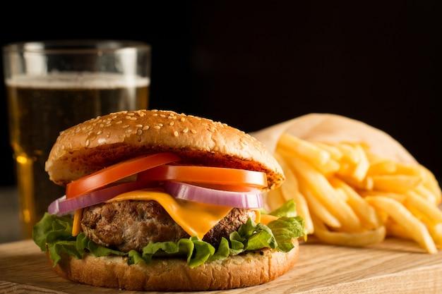 Hausgemachter hamburger mit rindfleisch, zwiebeln, tomaten, salat und käse. frischer burger nah oben auf hölzerner rustikaler tabelle mit kartoffelfischrogen, bier und chips. cheeseburger.