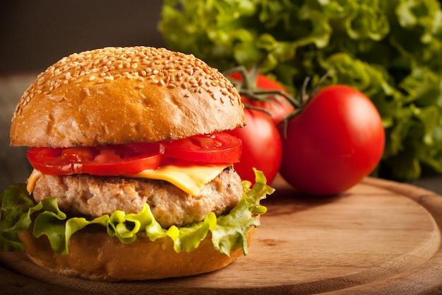 Hausgemachter hamburger mit rindfleisch, zwiebeln, tomaten, salat und käse. frischer burger nah oben auf rustikalem holztisch mit kartoffelpommes, bier und pommes. cheeseburger.