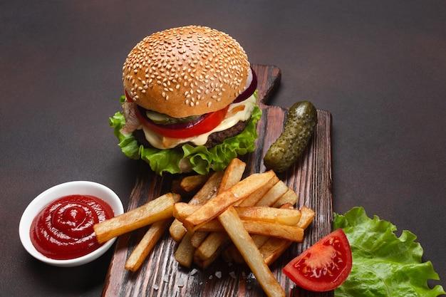 Hausgemachter hamburger mit zutaten rindfleisch, tomaten, salat, käse, zwiebeln, gurken und pommes frites auf schneidebrett und rostigem hintergrund. ansicht von oben.
