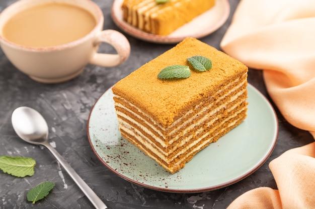 Hausgemachter honigkuchen mit milchcreme und minze mit tasse kaffee auf einer schwarzen betonoberfläche und orangefarbenem textil