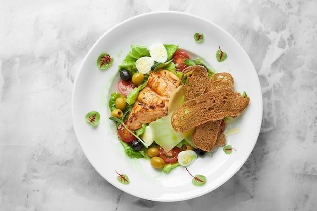 Hausgemachter hühnchen-caesar-salat mit käse und croutons, draufsicht.