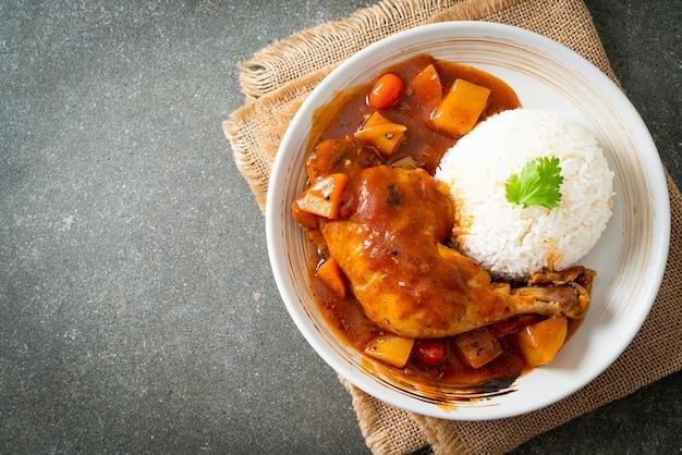 Hausgemachter hühnereintopf mit tomaten, zwiebeln, karotten und kartoffeln auf teller mit reis