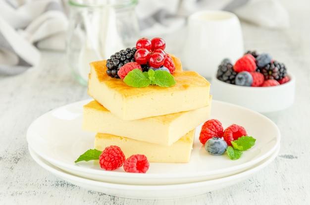 Hausgemachter hüttenkäse-auflauf mit frischen beeren und minze auf einem weißen teller. gesundes frühstück. horizontaler kopierbereich.