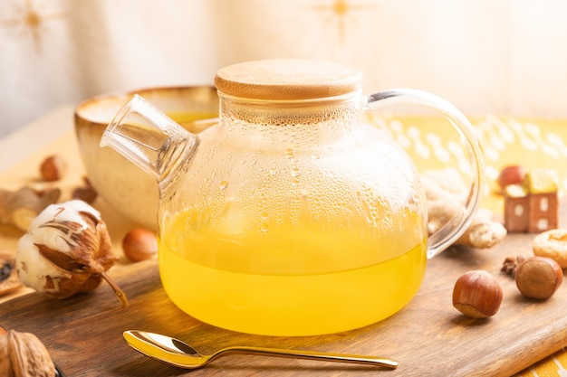 Hausgemachter ingwertee mit honig in der glasteekanne