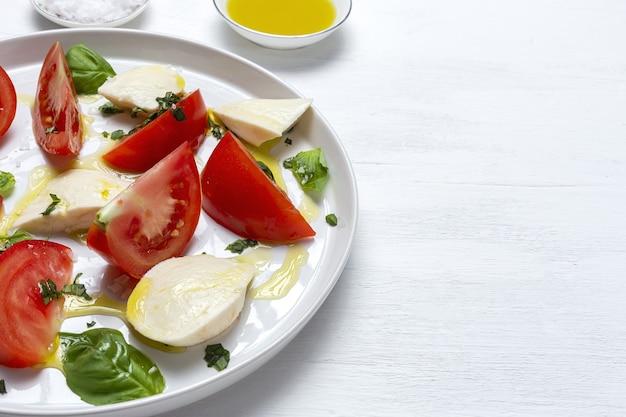 Hausgemachter italienischer caprese-salat mit geschnittenen tomaten, mozzarella, basilikum, olivenöl und salz.