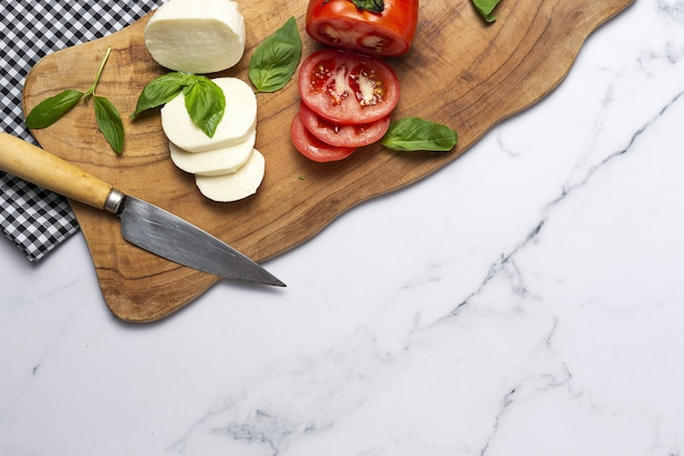 Hausgemachter italienischer caprese-salat mit geschnittenen tomaten, mozzarella-käse, basilikum