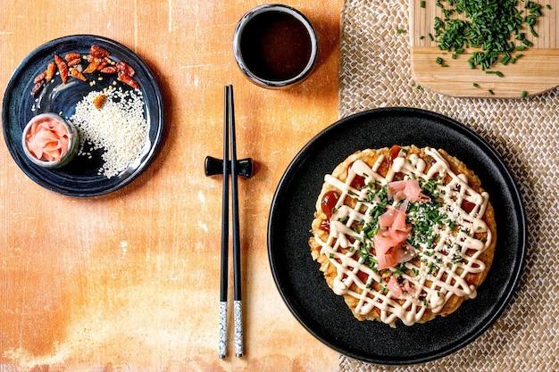 Hausgemachter japanischer fast-food-okonomiyaki-kohlpfannkuchen, dekoriert mit frühlingszwiebeln, eingelegtem ingwer, mayo-sauce auf schwarzem keramikteller mit essstäbchen und zutaten darüber. textur tabelle. flach liegen