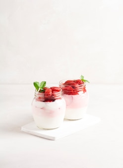 Hausgemachter joghurt mit reifen erdbeeren, dekoriert mit minzständern in banken auf einem holzständer