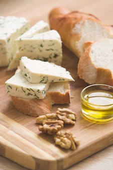 Hausgemachter käse und walnüsse olivenöl und brot auf einem holzbrett gepökelter quark auf dem tisch