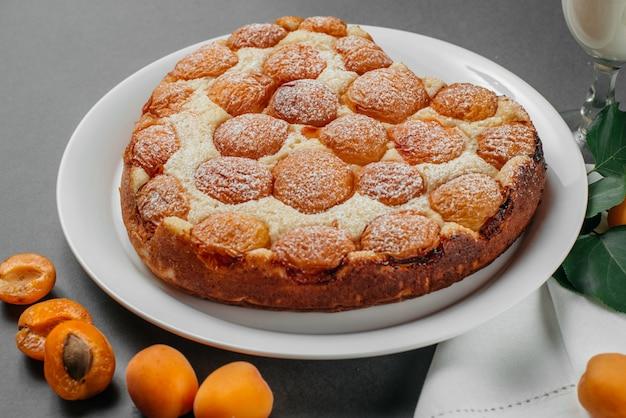Hausgemachter käsekuchen mit aprikosen auf grau
