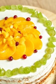 Hausgemachter karamellkuchen mit früchten. holzhintergrund.