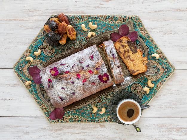 Hausgemachter kuchen mit datteln und nüssen, serviert mit schwarzem kaffee auf einem weißen holztisch